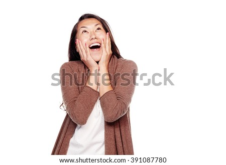 Young surprised asian woman wearing brown cardigan, standing with hands on her head and looking up with wide open mouth isolated on white background - astonishment concept - stock photo
