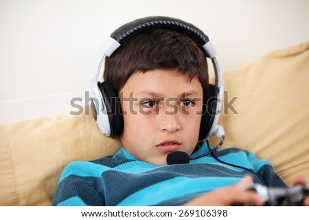 Young surprised boy playing video game with his friends with headset and microphone with copy space - stock photo