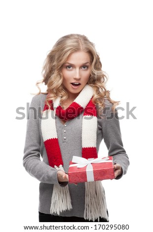 young surprised casual blond woman holding red christmas gift isolated on white - stock photo