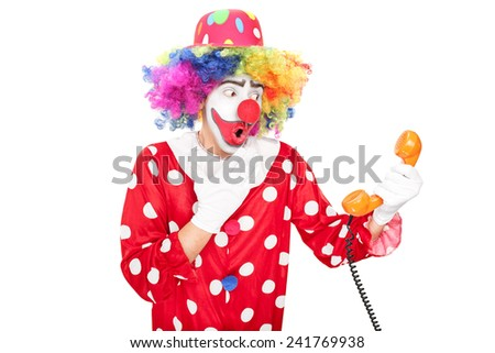 Young surprised clown holding a telephone speaker isolated on white background