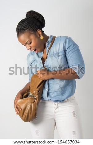 Young surprised model is looking in her handbag - stock photo