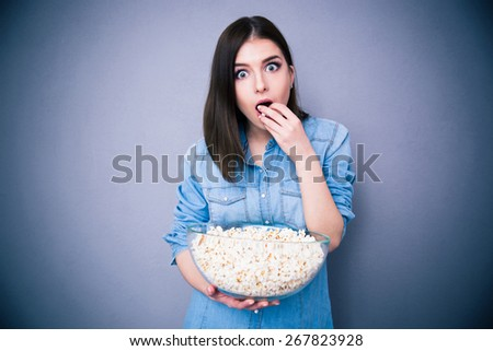 Young surprised woman eating popcorn over gray background. Looking at camera - stock photo