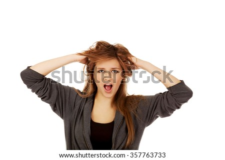 Young surprised woman holding hands inside hair.