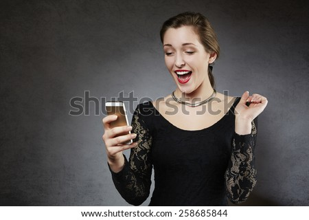 Young surprised woman receiving text message - stock photo