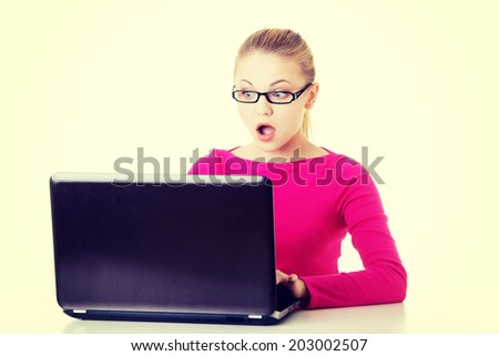 Young surprised woman sitting in front of laptop. Isolaed on white.