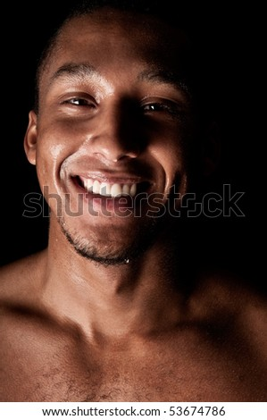 Young sweaty smiling male on black background - stock photo