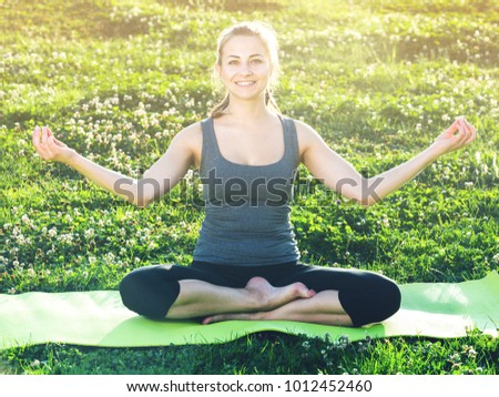 Young Swedish Female Doing Yoga Poses On Sunny Morning In The Green Garden