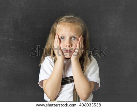 young sweet junior schoolgirl with blonde hair crying sad and shy standing isolated in front of school class blackboard wearing school uniform in children education stress and bullying victim - stock photo