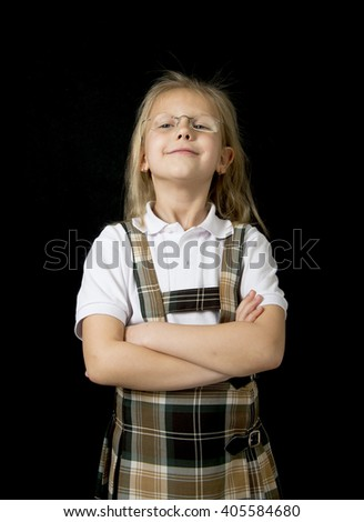 young sweet junior schoolgirl with blonde hair standing happy and smiling isolated in black background wearing school uniform in children education success and fun - stock photo