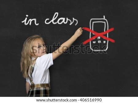 young sweet junior schoolgirl with blonde hair standing happy and smiling writing with chalk about not using mobile phone in school class in education rules and cellular forbidden concept - stock photo