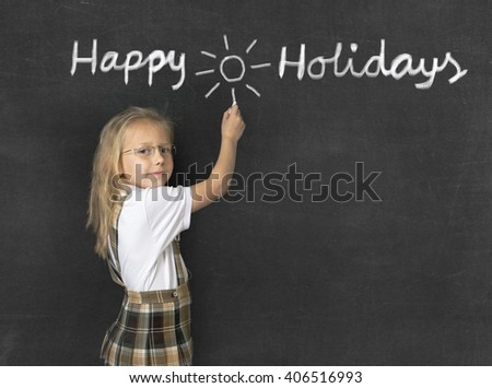 young sweet junior schoolgirl with blonde hair standing happy and smiling writing with chalk happy holidays drawing a sun in classroom blackboard wearing school uniform