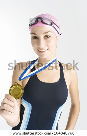 Young swimmer holding a gold medal while wearing a swimming costume, rubber hat and goggles, and smiling at the camera. - stock photo