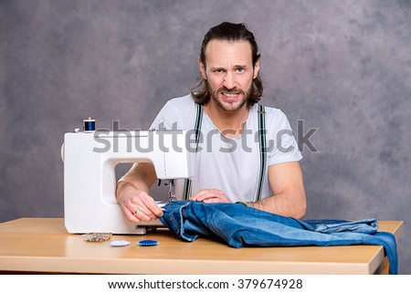 young tailor with sewing machine in front of gray background - stock photo