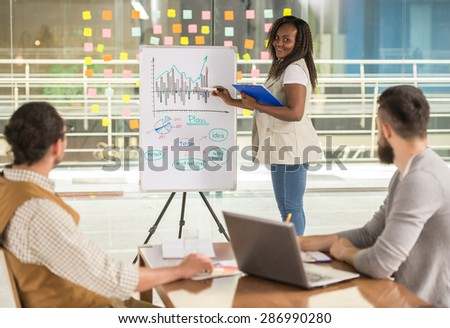 Young talented woman presenting to business partners new project. - stock photo