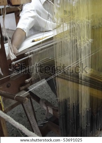 Young Tamil man weaves silk brocade on a Jacquard loom in Kanchipuram, Tamil Nadu, India, Asia - stock photo