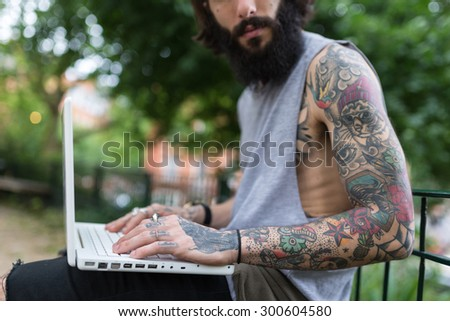 Young tattooed man portrait using laptop in Shoreditch borough. London, UK. Hipster style. - stock photo