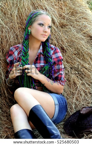 young tattooed  stylish woman with dreadlocks in cowgirl style,relaxing on haystack