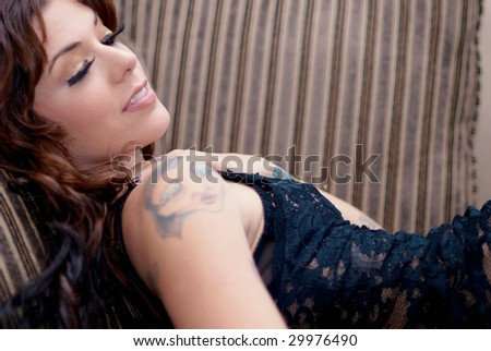 Young tattooed woman lying on old sofa - stock photo