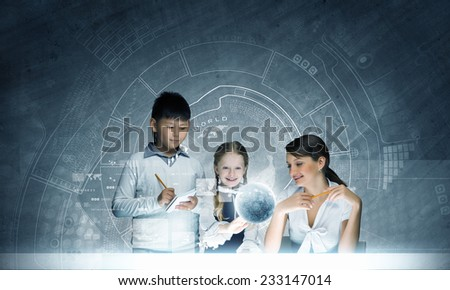 Young teacher and school children examining hologram. Elements of this image are furnished by NASA - stock photo