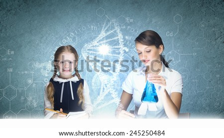 Young teacher and school girl at chemistry lesson - stock photo