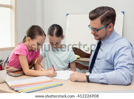 Young teacher and two schoolgirls study in classroom. Education, profession, homeschooling concept