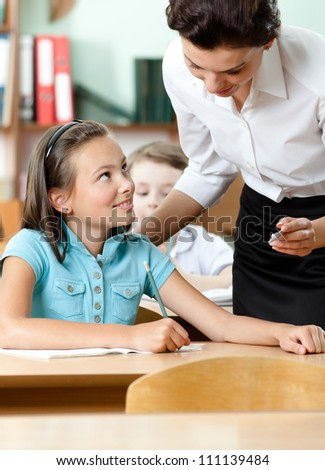 Young teacher answers to all the questions of the pupils concerning the task - stock photo