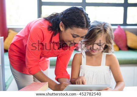 Young teacher assisting girl using digital tablet in school library - stock photo