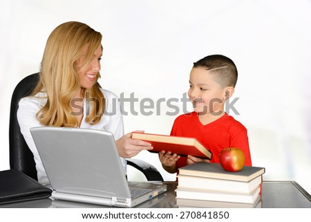 Young teacher handing a book to her student - stock photo