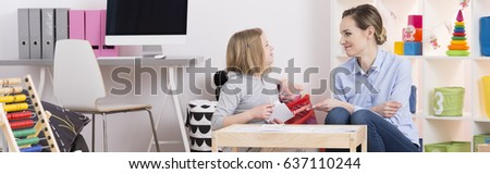 Young teacher helping little girl with her homework