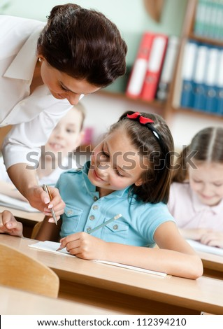 Young teacher helps pupils to do the task - stock photo