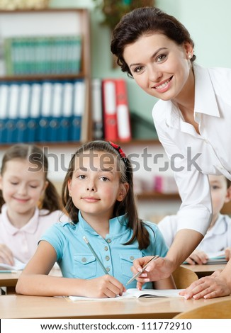 Young teacher helps pupils to perform a difficult task - stock photo