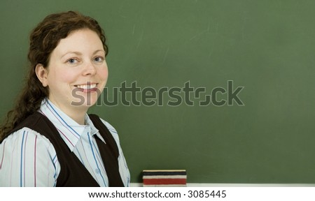 Young teacher in front of a chalkboard