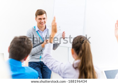 young teacher man talking with students in the classroom - stock photo