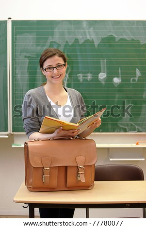 Young teacher or student in the classroom or university is smiling with book and bag in front of a blackboard - stock photo