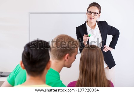 Young teacher pointing on a talking student - stock photo