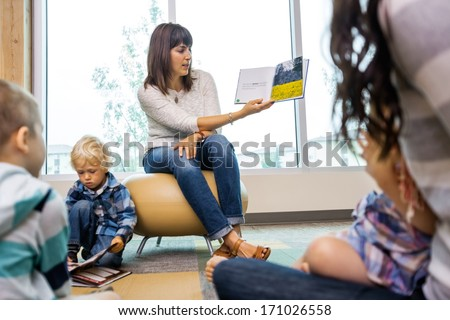 Young teacher reading book to students in library of elementary school - stock photo