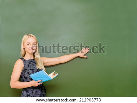 young teacher showing on chalkboard