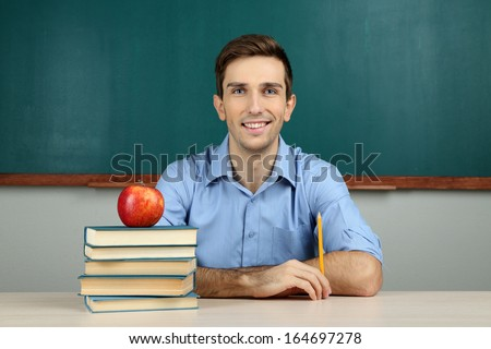 Young teacher sitting in school classroom - stock photo