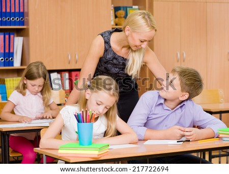 young teacher supervises the students during the exam - stock photo