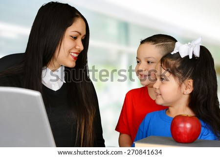 Young teacher talking to boy and girl - stock photo