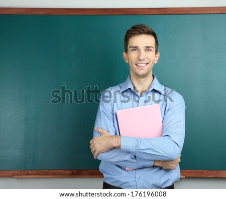 Young teacher with book near chalkboard in school classroom