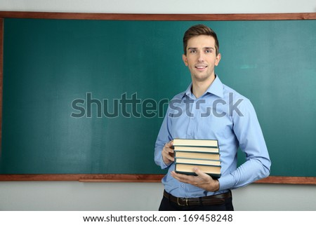 Young teacher with books near chalkboard in school classroom