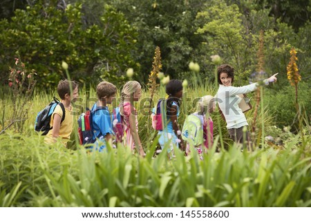 Young teacher with children on nature field trip