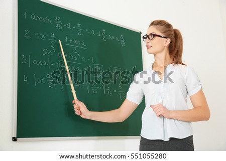 Young teacher with pointer beside blackboard on white background