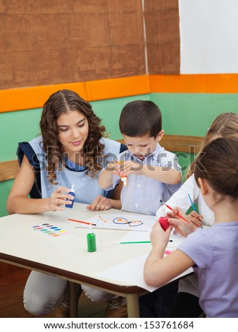Young teacher with students painting at desk in kindergarten - stock photo