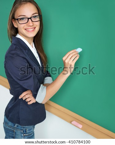Young teacher writing on blackboard. Photo of young woman, creative concept with Back to school theme - stock photo