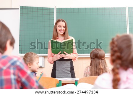 Young teacher. Young pleasant women teaching at school in junior school. - stock photo