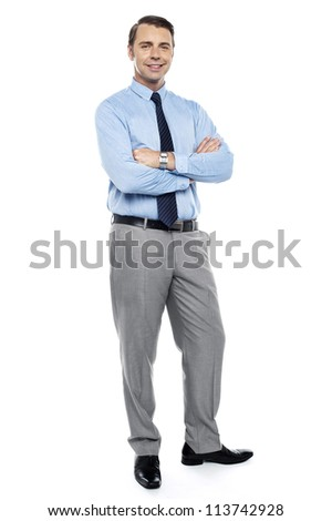 Young team leader smiling confidently with his arms crossed isolated against white. Full length shot - stock photo
