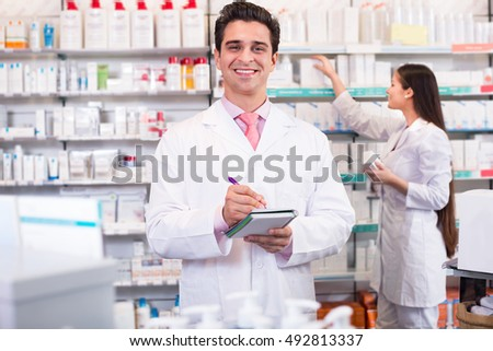 Young team of a pharmaceutist and a technician working at the chemist shop