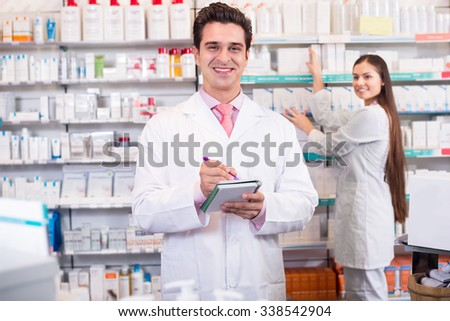 Young team of a pharmacist and a technician working at a chemist shop